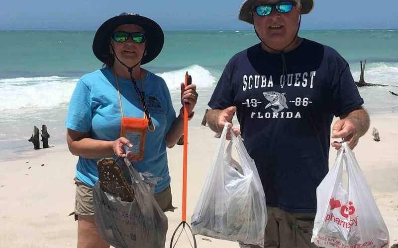 Volunteers holding trash bags after cleaning up Longboat Pass beach