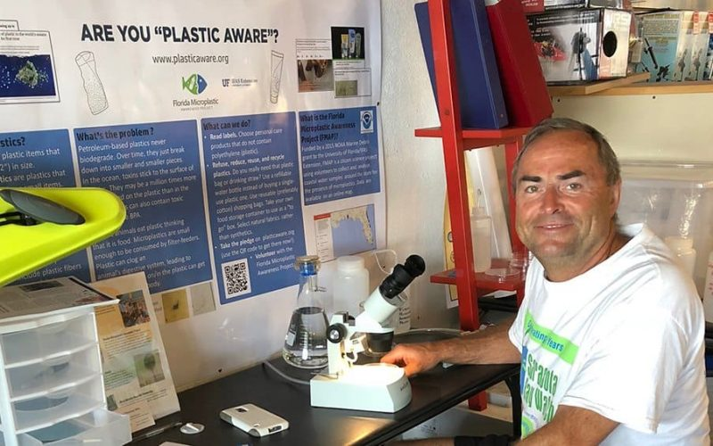One of the fantastic Happy Paddler volunteers for the Florida Microplastics Awareness Project sitting in front of the microscope